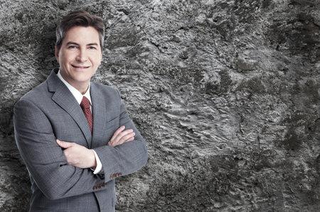 Executive businessman over grey wall background. 免版税图像