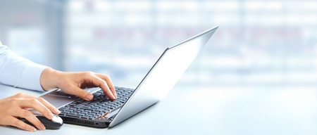 コンピューターのキーボードで入力するビジネスの女性の手。