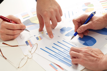 Hands of business people working with graphs. Teamwork. Stock Photo