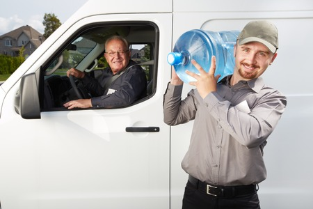 Water delivery service man with big bottle. Banco de Imagens
