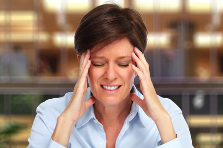 Tired business woman with headache migraine over house background Stock Photo