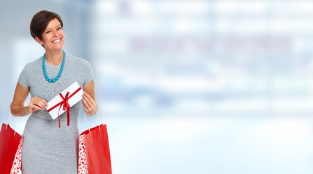 Smiling woman with shopping bags over blue banner background.