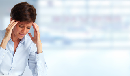 Tired business woman with headache migraine over blue banner. Reklamní fotografie