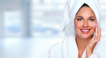 Beautiful woman face with moisturising cream. Skin care background.