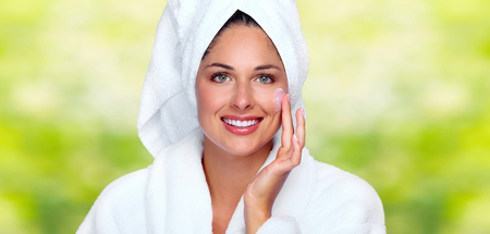 Beautiful woman face with moisturising cream. Skin care background.