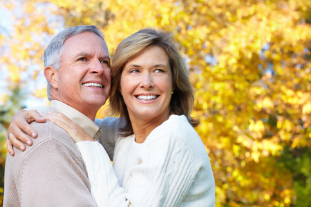 Happy senior couple in park. Autumn and fall background.