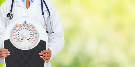 Medical doctor woman with scales. Diet and weight loss concept. Stock Photo