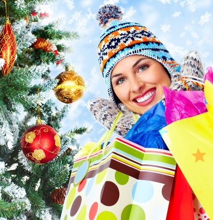 Shopping woman with a bags over Xmas winter background. 写真素材