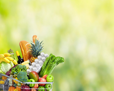 Grocery shopping cart with vegetables over green background. Stock Photo