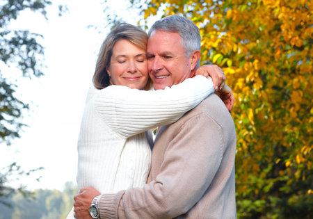 公園で幸せな先輩カップル。秋と秋の背景。