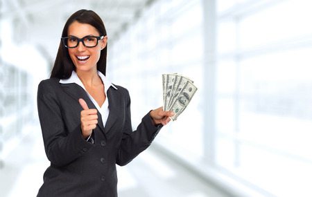 Happy laughing woman holding dollars over blue background 版權商用圖片