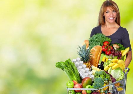 緑の背景の上の野菜の紙バッグを持つ女性。 写真素材