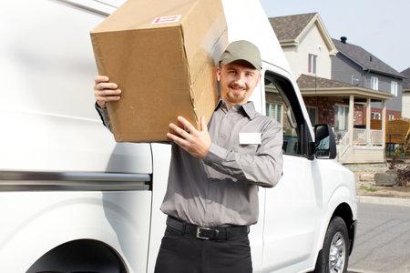 Jonge levering man met pakket in de buurt van cargo truck. Scheepvaart service. Stockfoto