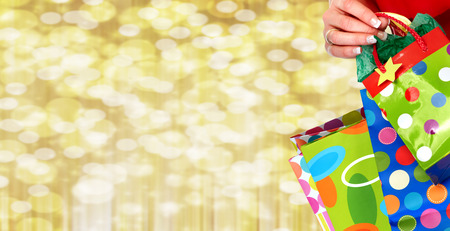 Woman hand with shopping bags over Christmas background. Stockfoto