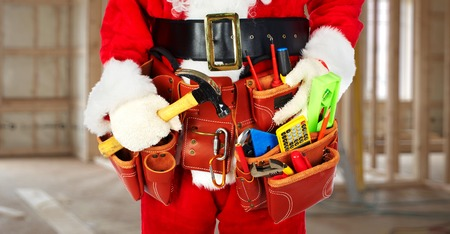 Santa Worker with a tool belt construction background.