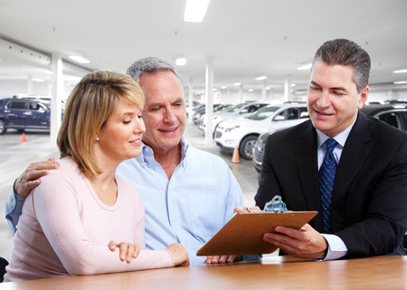 Senior smiling couple with car dealer. Auto rental background.
