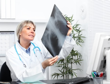 Mature medical doctor woman over hospital background.