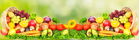 Fruits and vegetables over green background. Healthy diet.