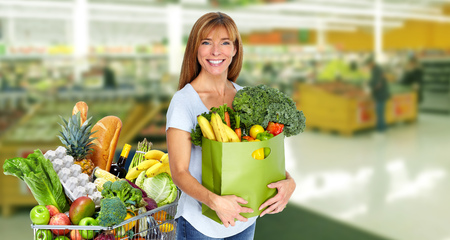 Woman with paper bag of vegetables over grocery store background.