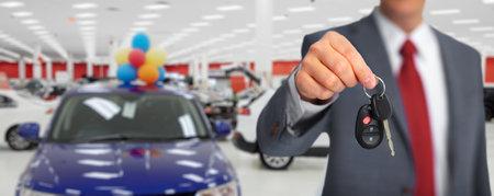 Hand met een autosleutel. Auto dealer en verhuur concept achtergrond. Stockfoto
