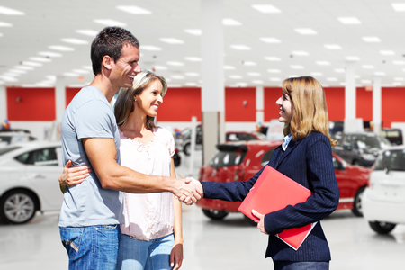 Young couple with a car dealer. Auto dealership and rental concept background.