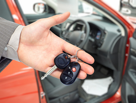 Hand with a car key. Auto dealership and rental concept background. Stok Fotoğraf - 47490158
