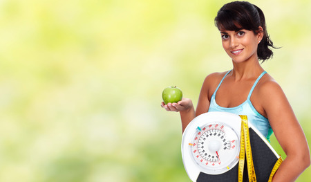 Young woman with apple and scales. Healthy diet and weight loss.