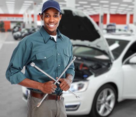 Sorridente garagista con chiave inglese in servizio di riparazione auto. Archivio Fotografico - 47490193
