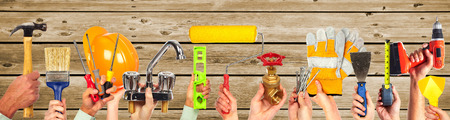 Hands of handyman with tools. House renovation and construction. Banco de Imagens