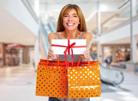 封筒とショッピング モールでのギフト ショッピングの女性。