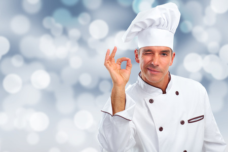 Handsome Chef man over abstract Christmas background. Stock Photo