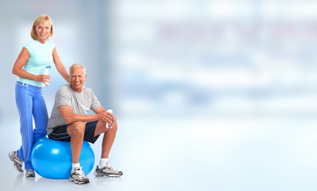 Senior healthy fitness couple. Over blue background 스톡 콘텐츠