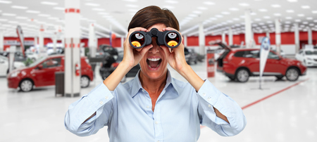 Business woman with binoculars over new cars background. Stock Photo