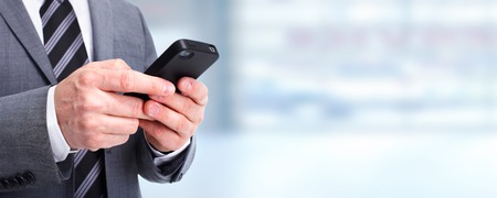Hands of businessman calling by phone over blue background. Imagens