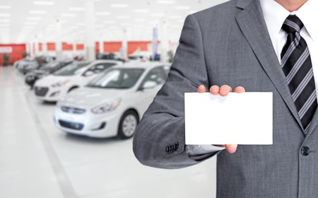 Auto dealer with a business card over vehicles background.