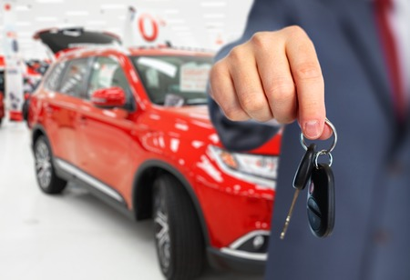 Car dealer with a key. Auto dealership and rental concept background. Archivio Fotografico