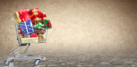 Shopping cart  with gifts over Christmas background. Stock Photo