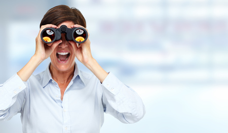 青い背景の上の双眼鏡とビジネスの女性。 写真素材