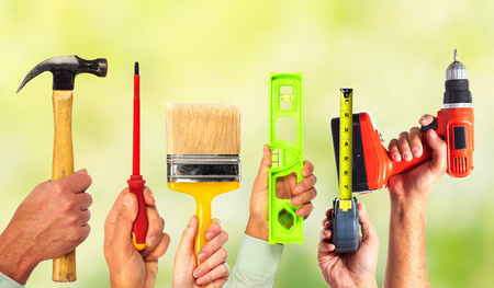 Hands of handyman with tools. House renovation and construction. 스톡 콘텐츠