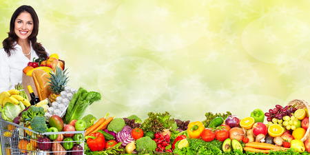 Young woman with vegetables over green background. Healthy diet.