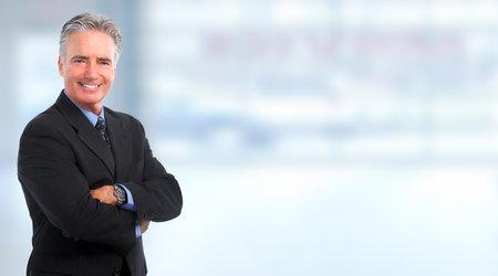 青い背景に笑顔の成熟したビジネスマン