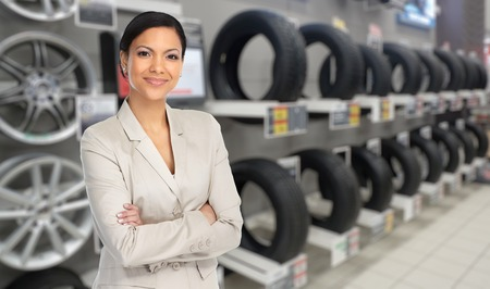 Beautiful agent woman in car repair service over tire background. Archivio Fotografico