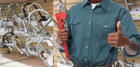Plumber hands with a pipe wrench over plumbing tools background. Stock Photo