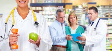 의료 배경 위에 아령과 사과와 의사 여자. 스톡 콘텐츠
