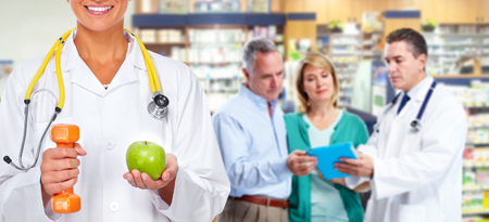 Doctor woman with dumbbell and apple over health care background.