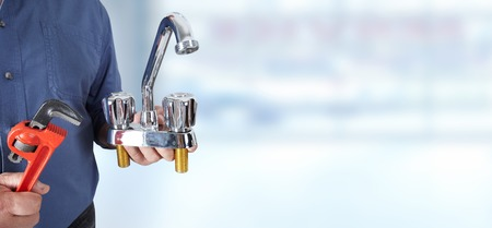 Plumber hands with water tap over blue background. Reklamní fotografie - 49257103