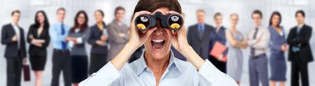 Business woman with binoculars over people group background. 版權商用圖片