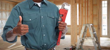 Mains de plombier avec une clé à tuyau sur fond nouvelle maison. Banque d'images - 49257061