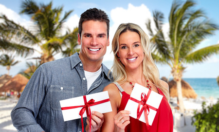 Couple with  envelope Christmas gift over tropical beach background. Foto de archivo