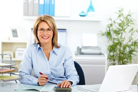 Beautiful mature business woman working in modern office. Stock Photo